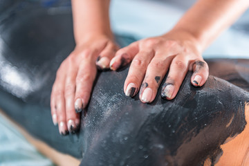 Mud massage with hands on body. Fototapete