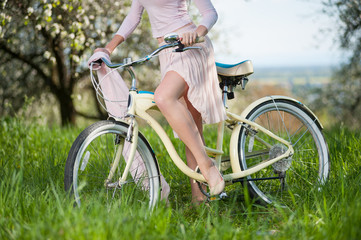 Close-up of perfect bend leg of pretty girl in white dress sitting on vintage bike against fresh greenery on blurred background of spring garden