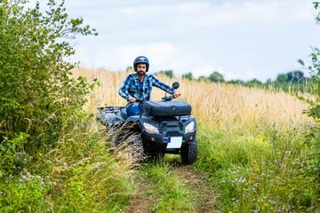Mann fährt Off-Road mit Quad ATV durch Gelände