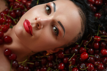 Girl bodybuilder on the background of ripe red cherries