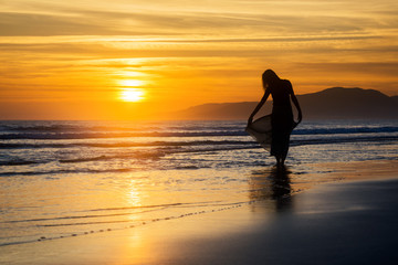 Girl at sunset holding her long dress in the sea waves silhouette