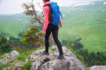 Young Woman Traveler with Backpack hiking in Mountains with beau