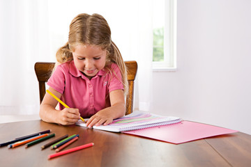 Education: Cute Girl Drawing Rainbow At Table With Colored Penci