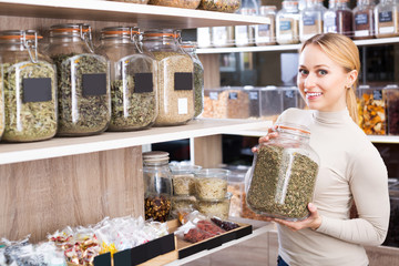 Woman choosing dried herbs
