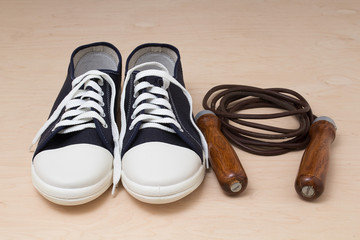Sneakers and jump rope on a light wooden background