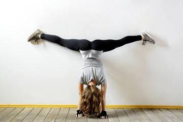 Fit woman doing a handstand near the wall. Fitness workout. Concept balance sport fitness. Female in sportswear with long blond hair. View from the back.