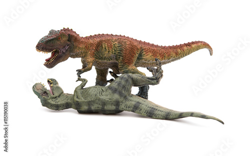 two tyrannosaurus toys on a white background, one stands and the other lays down