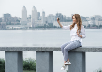 trendy young woman makes the photo on the phone on the backgroun