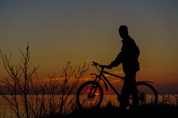 Dark silhouette of a cyclist on the beach