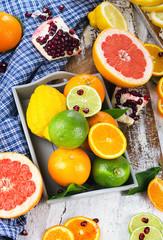 Fresh citrus fruits on white wooden board.
