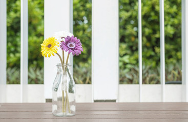 Closeup artificial colorful flower on transparent glass bottle on wood chair in the garden view background