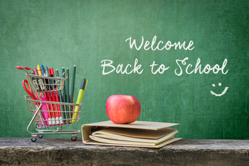 Welcome back to school: Shopping cart, student supplies, stationery, notebook, apple on dark wood top and grunge green chalkboard background