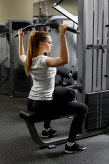 A young trained girl building biceps in a gym. Training for strength of the back muscles
