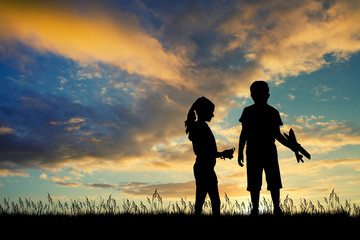 children qith kite and airplane at sunset