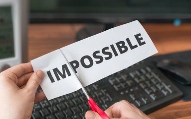 Possibility, success and challenge concept. Man is cutting paper with impossible word to make it possible.