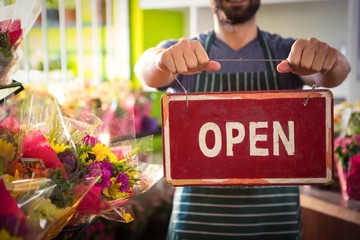 Male florist holding open signboard at his flower shop