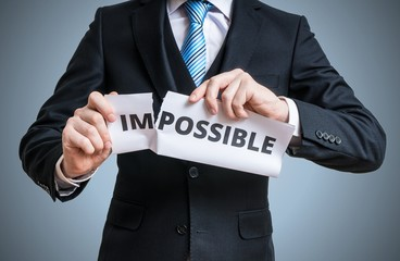 Possibility concept. Businessman is tearing paper with impossible word to make it possible.