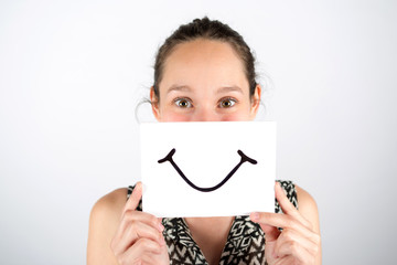 Happy woman smile hidden behind a board isolated on a white back