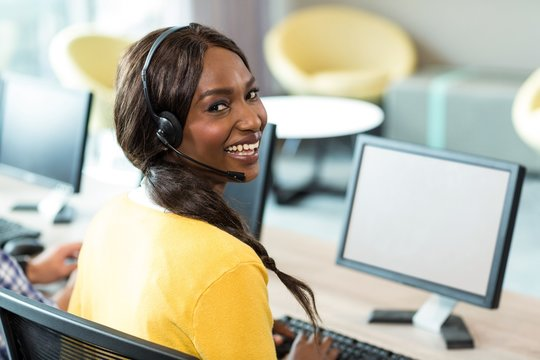 Young woman working on computer with headset