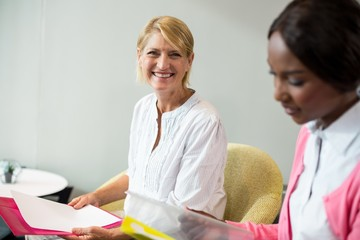 Woman smiling at camera while her colleague reading document
