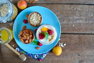 Homemade yogurt with granola, almonds, peaches and raspberries o