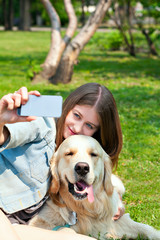 Girl and her dog selfie summer on a background of green grass