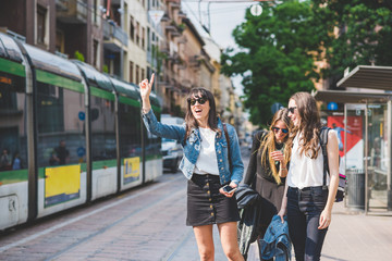 Three young beautiful caucasian women friends outdoor in the city smiling and having fun, asking for a taxi - commuter, students, having fun concept