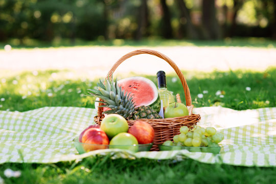 Composition of a basket with fruits and wine in the park