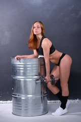 Beautiful young girl with an ideal figure and dumbbell in hand leans the elbows on barrel