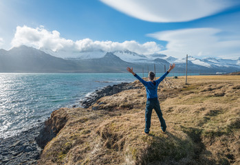 The man standing in front of the mountain range in East Iceland.