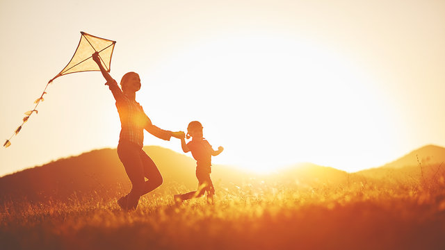happy family mother and child run on meadow with a kite in the s
