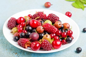 a variety of wild berries on a plate.selective focus