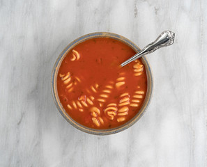 Rotini tomato soup in bowl with spoon on a gray marble cutting board.