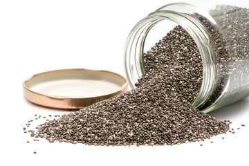 Chia seeds in an overturned glass jar with the lid next to it seen from front on white background