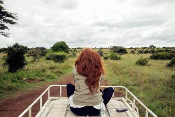 Woman enjoying ride on top of vehicle in wildlife park, Nairobi, Kenya