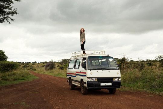 Woman standing on top of vehicle in wildlife park, Nairobi, Kenya