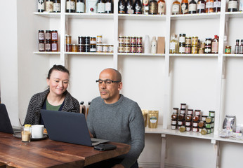 Couple sitting at cafe table browsing laptop
