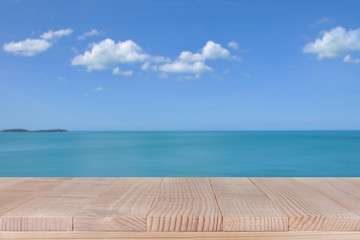 Wood table top on blurred blue sea with cloud background