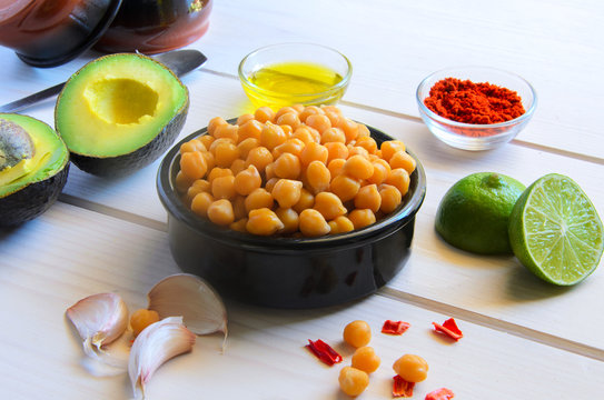 Ingredients for cooking delicious Avocado  hummus. Chickpeas, olive oil, lemon juice, garlic and spices on wooden background. Healthy eating.