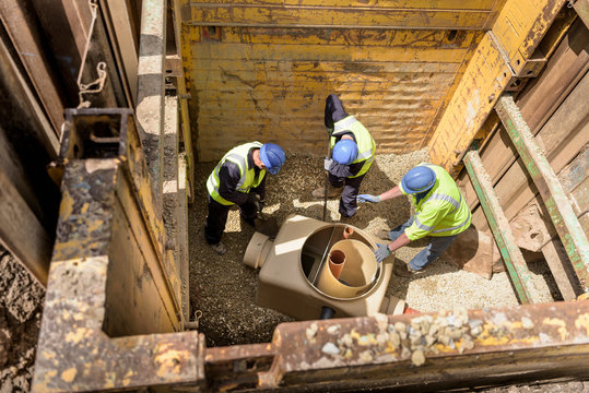 Apprentice builders training with drainage in hole on building site