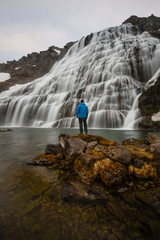 Man standing on rock, watching waterfall, Dynjandi waterfall, Westfjords, Iceland