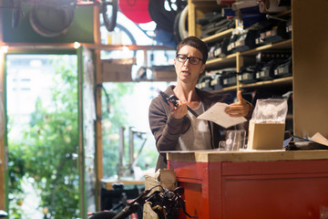 Woman at counter in bicycle workshop holding bike part and paperwork