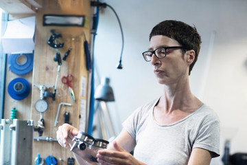 Woman in workshop looking at bicycle part