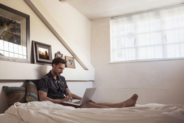 Man on bed using laptop