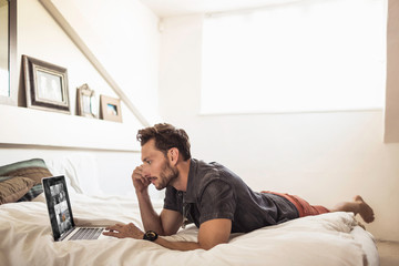 Man lying on bed using laptop