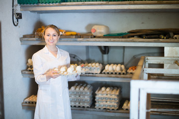 Happy woman holding carton tray with fresh eggs