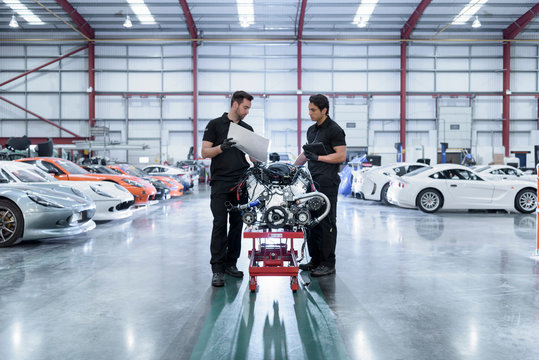 Engineers with engine for repair in racing car factory