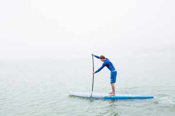 Young man stand up paddleboarding on misty lake Pilsensee, Germany
