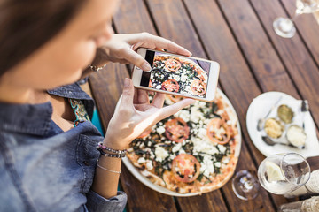 Woman taking pictures of pizza