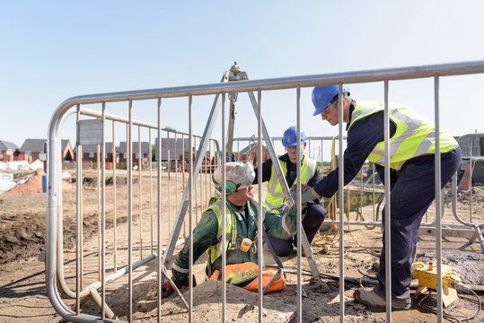 Apprentice builders assisting worker out of manhole on building site